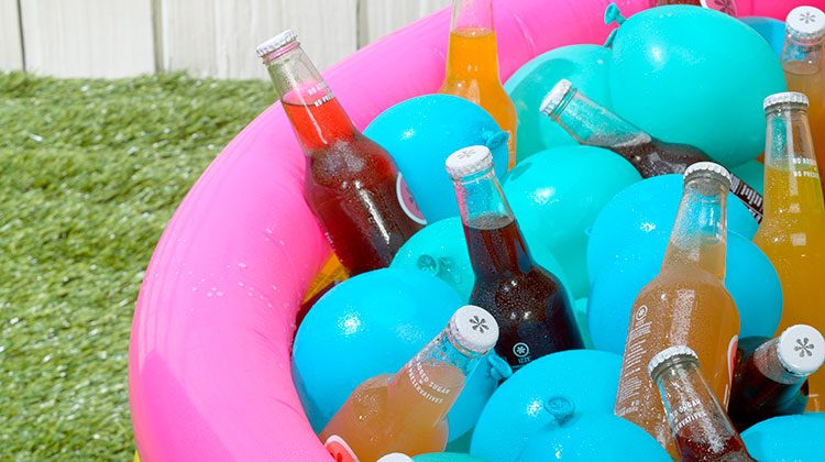 Soda bottles in a pink and yellow stripped, blow-up kiddie pool along with blue water balloons to keep them cool
