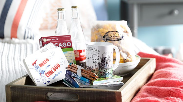 A welcome tray sitting on a guest bed filled with Chicago themed gifts such as a mug, guide books, welcome letter and soda