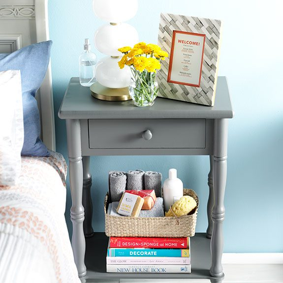 Night stand with a framed welcome note and flowers on top and books with assorted tolietries on a lower shelf
