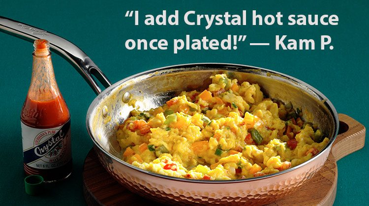 Scrambled eggs in a skillet with a bottle of hot sauce on the side and the words 'I add Crystal hot sauce once plated!' -- Kam P.