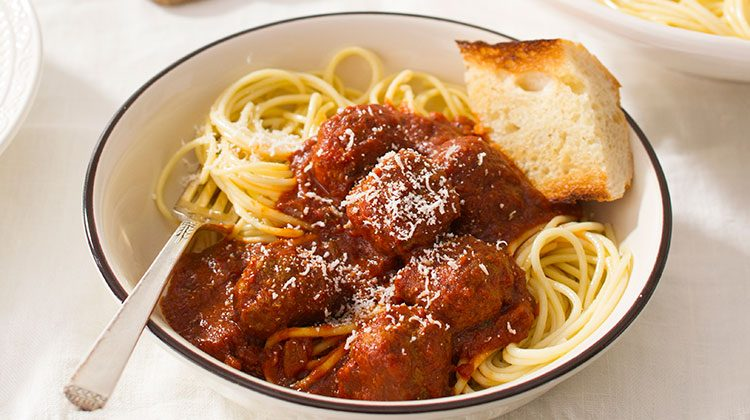 Spaghetti blanketed with sauce piled into a white bowl and a slice of garlic bread sits on top