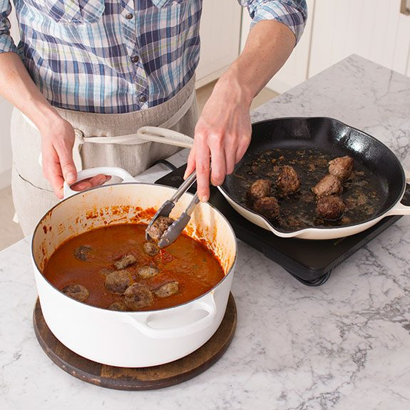 Using tongs, the person then transfers their meatballs into the dutch oven filled with their sauce to submerge them