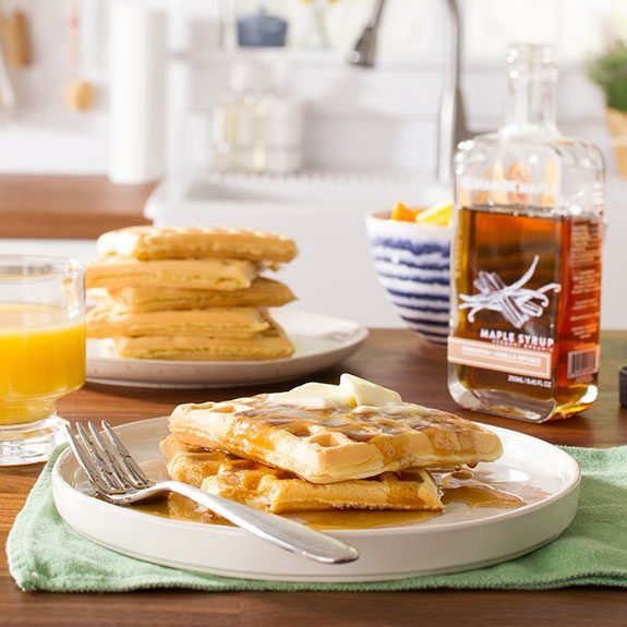 Two waffles covered in syrup and topped with butter sitting in front of a stack of waffles, glass of orange juice and a mostly full bottle of maple syrup