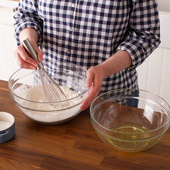 Person using a whisk to mix together the dry ingredients
