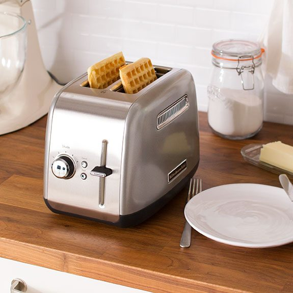 Two waffles sitting in the slots of a toaster with a plate and silverware ready beside the appilance