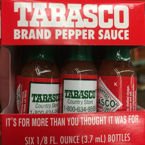 Small bottles of hot sauce in a little red cardboard carrying container