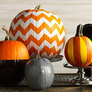 Multiple painted pumpkins of different sizes sitting together on a wooden table