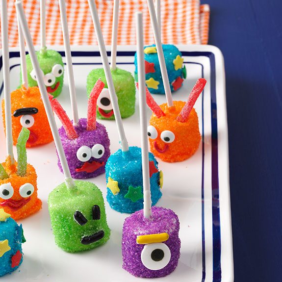 Multiple marshmallows coated in green, blue, purple and orange sugar then skewered with sticks and decorated with candy faces