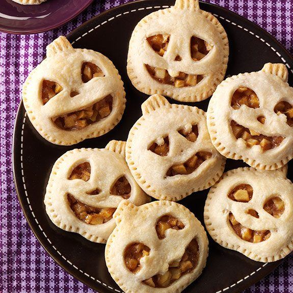 Mini maple pumpkin pies in the shape of jack-o-lanterns with different faces on a black plate on top a purple plaid table