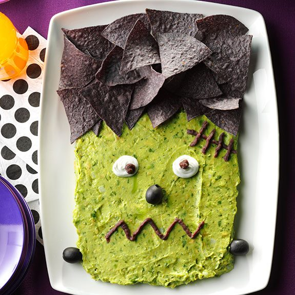 Rectangular white plate filled with guacamole and black corn chips as hair and a cute little face in the middle