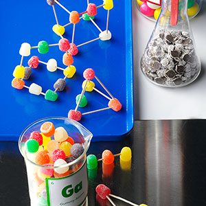 Gum drops hold up toothpick structures on a blue tray and two beakers on the side one with gumdrops and non-pariels
