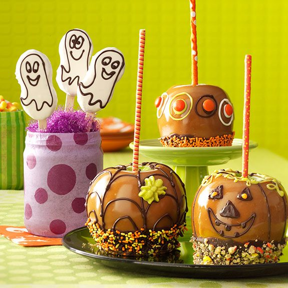 Two caramel apples on a black plate and another on a green platter overlooking them. All three have been dipped in chocolate and decorated to look like a pumpkin, covered in spiderwebs and eyeballs