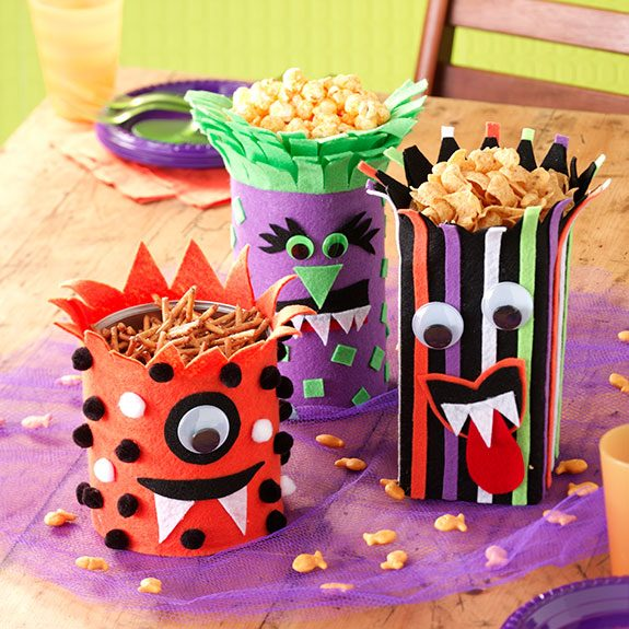 Three metal jars covered felt and multiple colored dots, stripes, fangs and cutesy faces