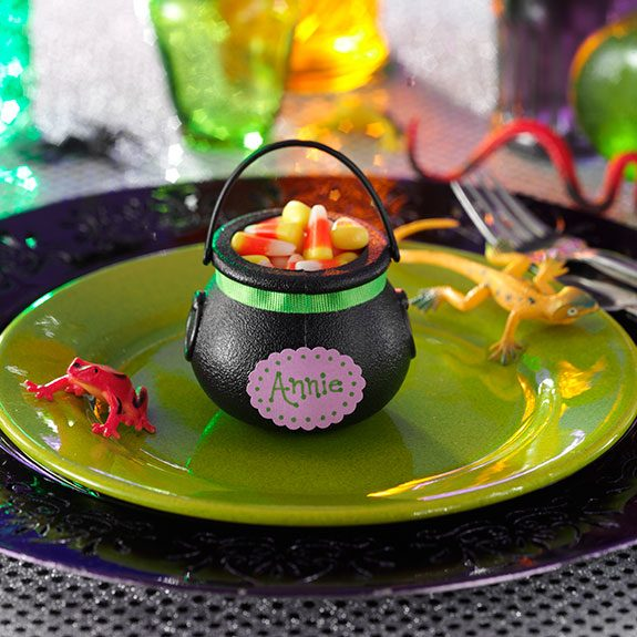 Little plastic cauldron filled with candy corn on a green plate lined with a fake lizard on one side and a fake frog on the other