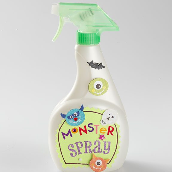 Spray bottle labeled 'Monster Spray' and covered in big, bright stickers of bats, skeletons and cyclops