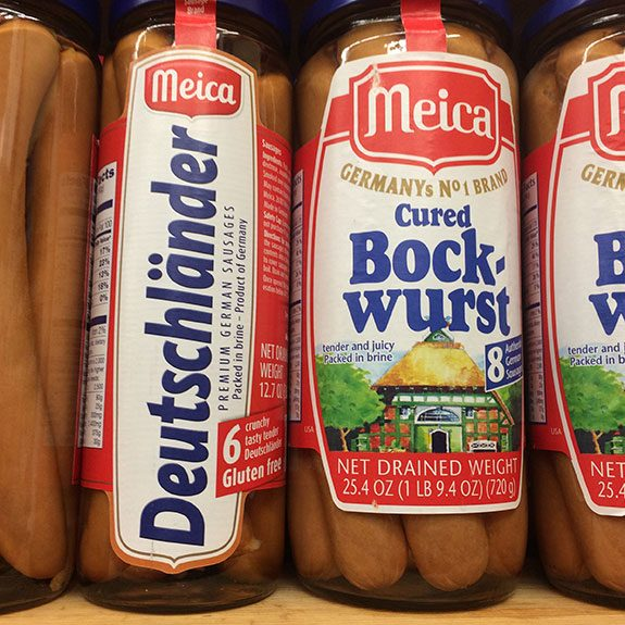 Tall jars of cured Bock-wurst packed in brine lined up on a wooden shelf