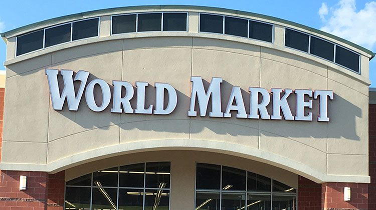 The outside of a World Market store the name of the store written in large white letters over brick pillars
