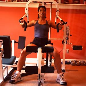 Woman working out at home with an exercise machine