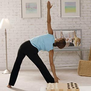 Woman following along to exercise video at home.