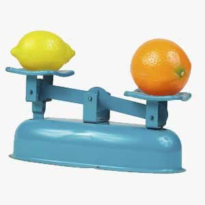 Lemon and orange balancing on scale