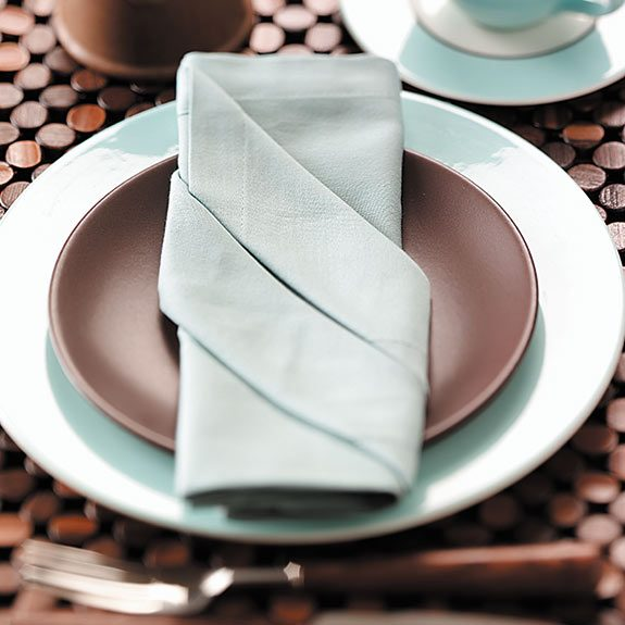 then fold the napkin into thirds with the folds forming a diagonal on the front