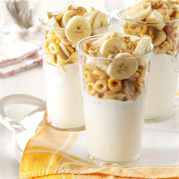 Three glasses with yogurt on the bottom and the top half with banana slices and cheerios