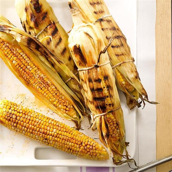 Unshucked corn on the cob with grill marks.