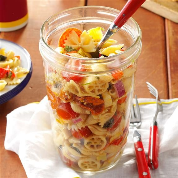 Pasta salad in a tall glass jar with a red-handled spoon dug halfway into it and a white towel crumbled underneath the jar on a wooden table