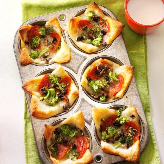 Muffin tin filled with miniature pizzas topped with pepperoni, broccoli and cheese