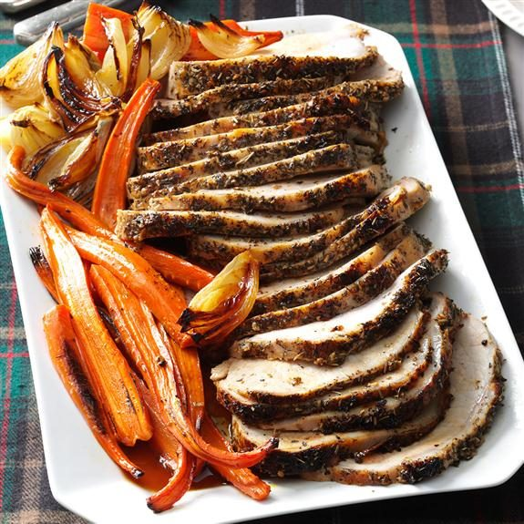 Thick slices of Italian Herb-Crusted Pork Loin lined up on a rectangular white plate with roasted veggies lining the left side