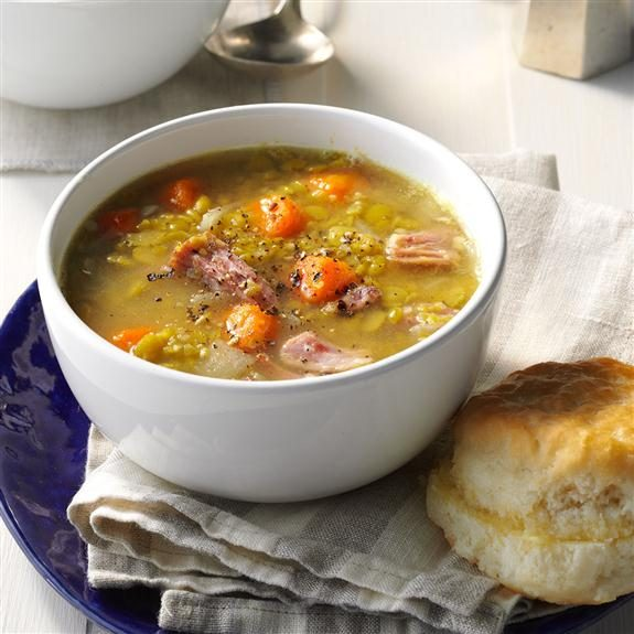Split pea soup with chunks of ham in a white bowl beside a biscuit on top a white towel on top a dark blue plate