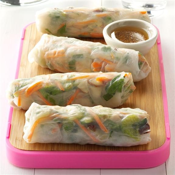 Four spring rolls sitting on a serving platter beside a small cup of sauce
