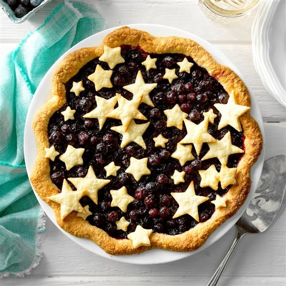 Beautiful blueberry pie with cutout stars of varying sizes arranged on top
