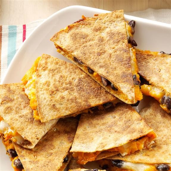 Sweet potato and black bean quesadillas cut into triangles and stacked together on a white, square plate