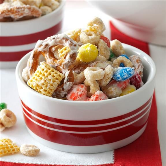 White and red striped bowl filled with white chocolate-covered trail mix